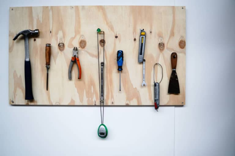 minimalist photography of hand tools hanged on wall